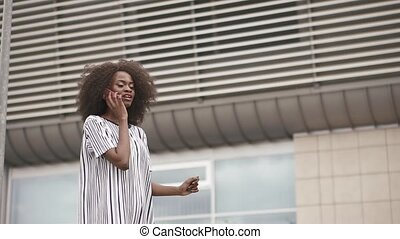 Gorgeous african american woman talks by phone on the massive airport wall background. Slow motion shooting