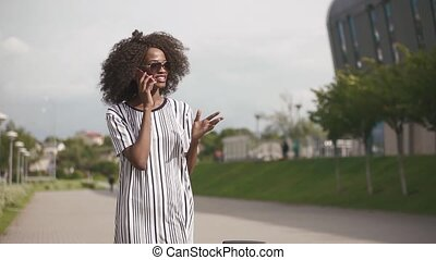 Young attractive african american business woman in sunglasses talking on mobile phone and smiling. Urban city background