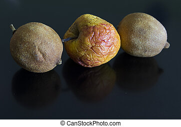 two lemons and a dried apple lined up on a black background...