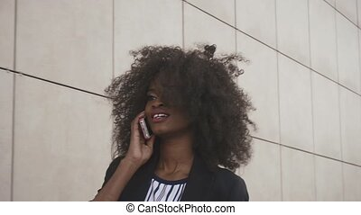 Attractive african american business lady talks by phone on...