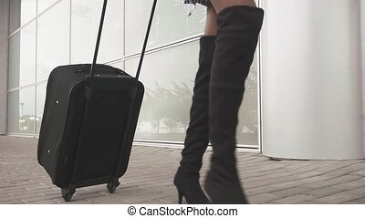 Close-up slim female legs in high black boots with black luggage going to the airport. Travel concept