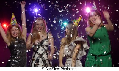 Young girls throwing glitter confetti and dancing fun -...