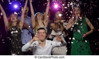 Young people dancing and throws glitter confetti at the...