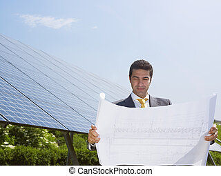 businessman standing near solar panels - Portrait of mid...