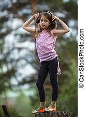 Little girl in headphones standing