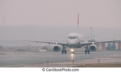 The Superjet 100 moving on a taxiway in the airport in a rainy day. Some airport facilities in the background