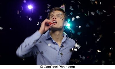 Guy throwing glitter confetti, blowing party whistle and...