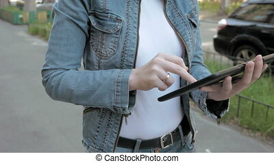 Woman types texts on tablet pc walking outdoors - Woman in...