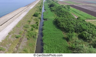 country road along the grassy river - aerial view of country...