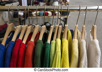 Colourful sweaters on clothes rack