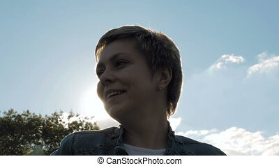 Portrait of blond short hair woman against the sun -...