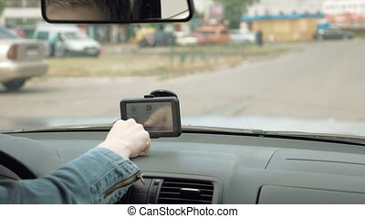 Woman programs the GPS navigator on the windshield - Woman...