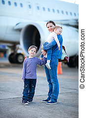 Family travelling - Young mother with two kids in front of...