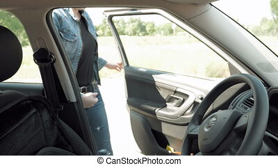 Woman driver in casual jeans cloth gets in a car