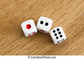 Photo of three white dices being rolled on wooden background