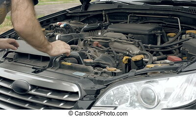Auto mechanic visually examines car motor engine - Man...