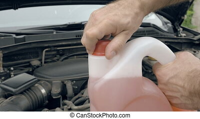 Opening bottle with pink windshield washer fluid - Man...
