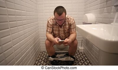 Man In Toilet Using Smart Phone - Man In Toilet writing sms...