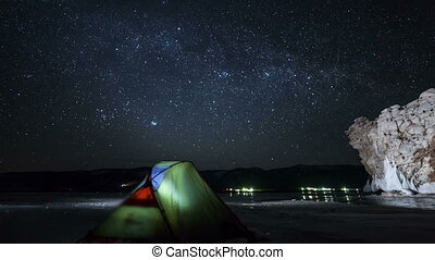 Moving stars above tent at night time lapse. Camera moving...