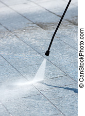 Using a pressure hose to power clean paving - Using a...