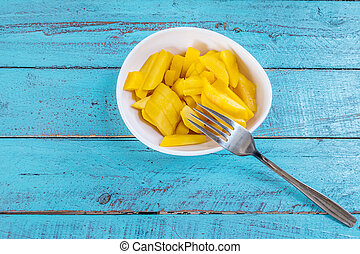 Ripe mango slices - Ripe mango slices in a cup on a blue...