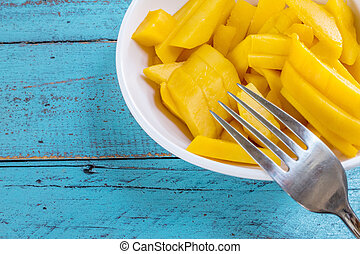Ripe mango slices. - Ripe mango slices in a cup on a blue...