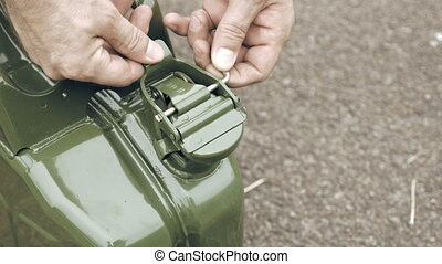 Man opens gas petrol or diesel jerry can with fuel and...