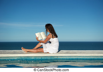 Relaxing reading - Woman reading a book on the wall of a...