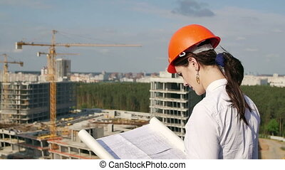 Woman architect inspects the construction site, checks the...