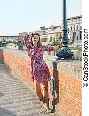 Happy woman walking along the embankment near Ponte Vecchio...