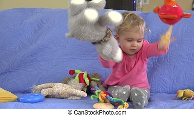 Little baby girl throwing soft toys from sofa Static closeup...