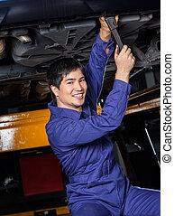Confident Mechanic Repairing Underneath Car - Portrait of...