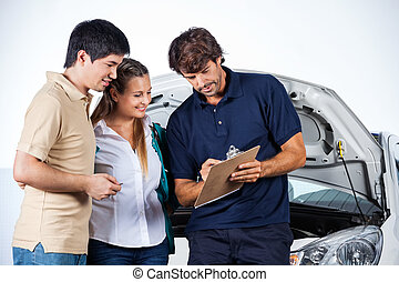 Mechanic Explaining Documents To Couple - Male mechanic...
