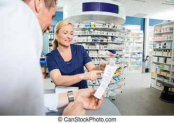 Pharmacist Explaining Details Of Product To Customer