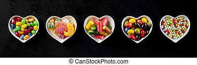 Candy banner in heart-shaped dishes over black - Assorted...