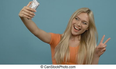 Selfie time! Cheerful young blonde woman making selfie on...