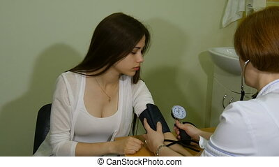 The doctor measures the pressure of the girl tonometer