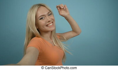 Close up portrait of young blonde girl holding a smartphone or digital camera with her hands and taking a selfie standing against blue background