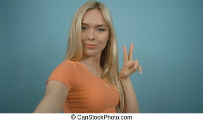 Smiling blonde girl in orange T-shirt taking selfie with grimace standing against blue background