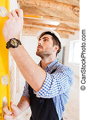 Close-up portrait of a construction builder holding yellow...