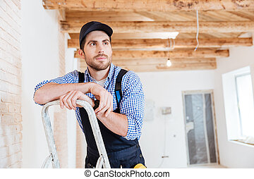 Handsome builder thinking about something while working