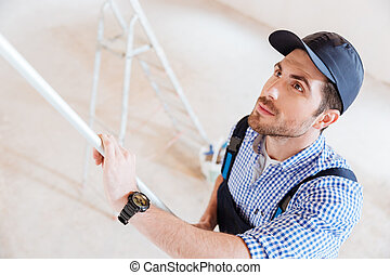 Close-up portrait of a decorator using roller in work