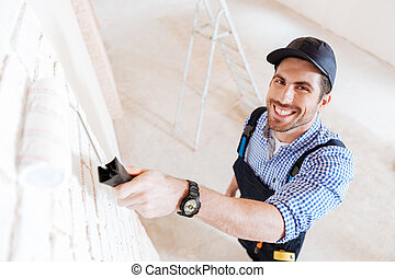 Close-up portrait of young handsome builder with paint roller