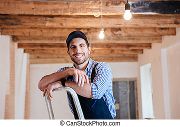 Smiling handyman standing on the ladder at the working area...