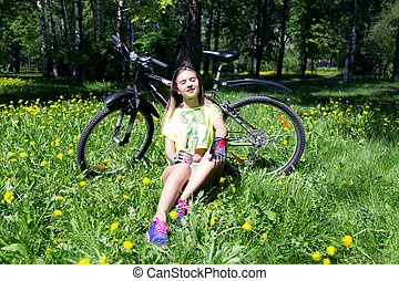 Portrait of pretty young woman with bicycle in a park - outdoor. girl sitting on the grass and drinks water from a bottle
