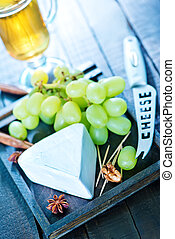 cheese with grape on a board and on a table