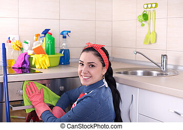 Cleaning lady wiping oven - Young pretty cleaning lady...