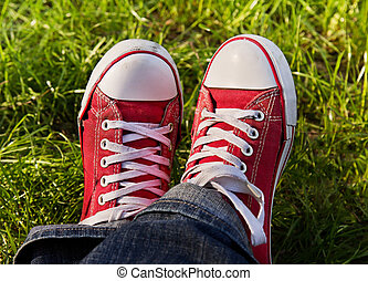 Feet in dirty red sneakers outdoors Making first step
