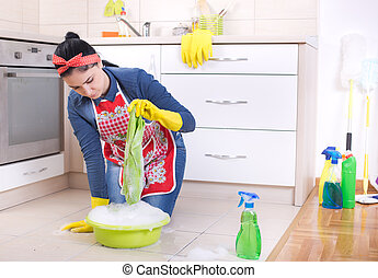 Woman cleaning kitchen floor - Young pretty woman cleaning...