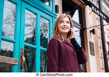 Cheerful woman walking in city and talking on cell phone -...